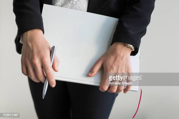 Midsection of woman holding file while standing at office