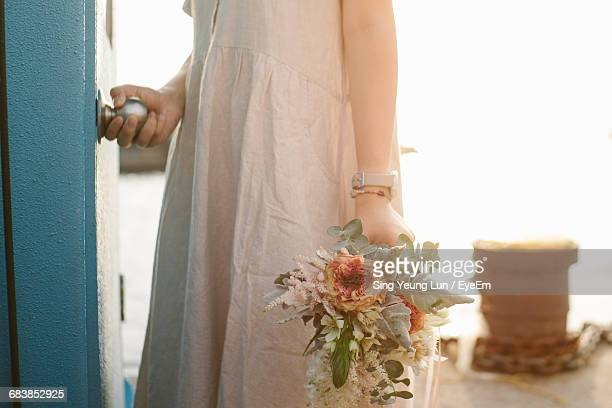 Midsection Of Woman Holding Flower Bouquet While Opening Doorknob