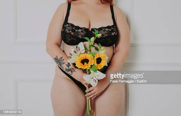 midsection of woman holding flower standing against wall - mutandine foto e immagini stock
