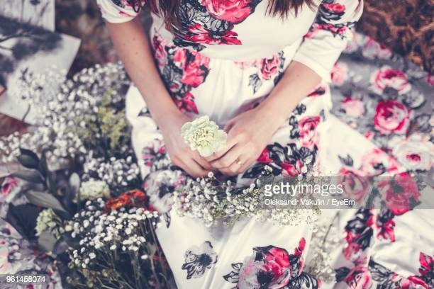 Midsection Of Woman Holding Flower While Sitting Outdoors