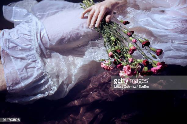 Midsection Of Woman Holding Flowers While Swimming In River