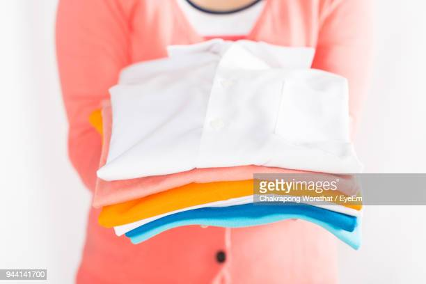Midsection Of Woman Holding Folded Shirts Against White Background