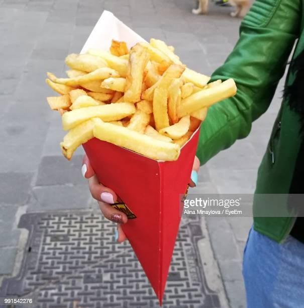 Midsection Of Woman Holding French Fries While Standing On Street