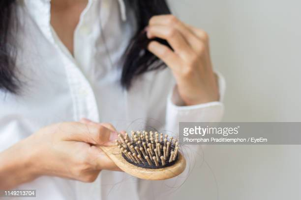 midsection of woman holding hairbrush against wall - hairbrush stock pictures, royalty-free photos & images