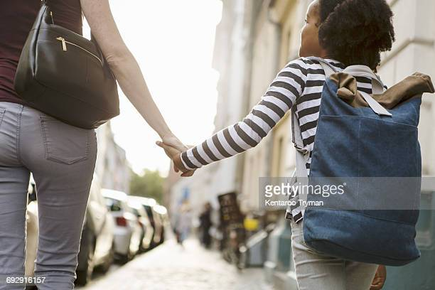 Midsection of woman holding hands with daughter while walking on sidewalk in city