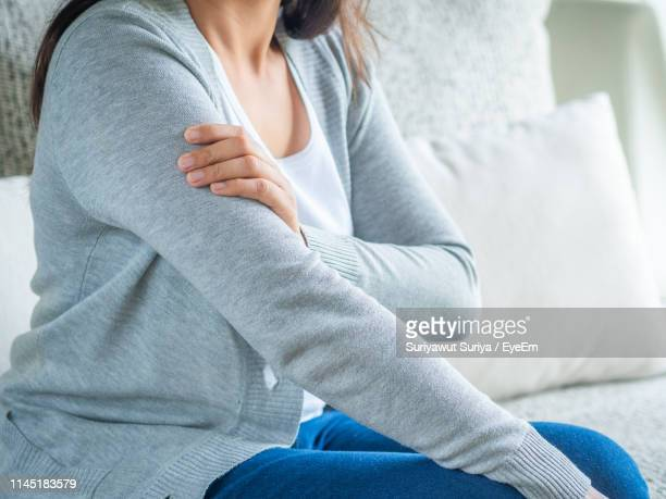 midsection of woman holding her arm - mid section stock pictures, royalty-free photos & images