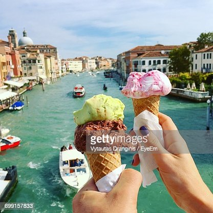 Midsection Of Woman Holding Ice Cream In City Against Sky