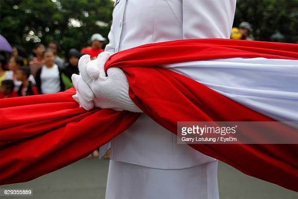 midsection of woman holding indonesian flag during parade - indonesia flag stock photos and pictures