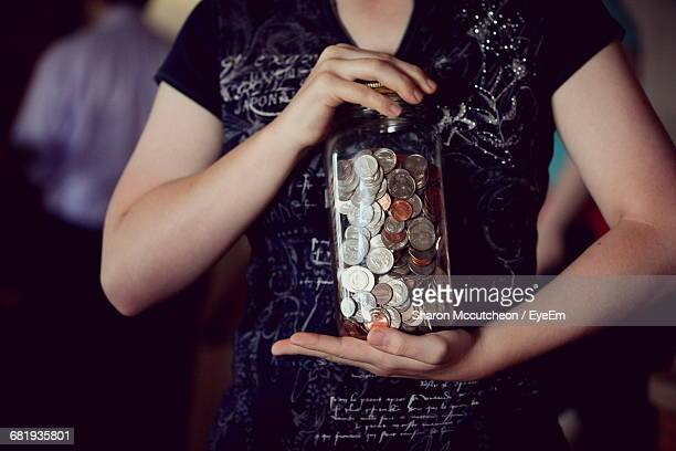 Midsection Of Woman Holding Jar Of Coins