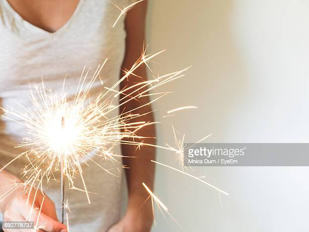 Midsection Of Woman Holding Lit Sparkler Against Wall During Christmas