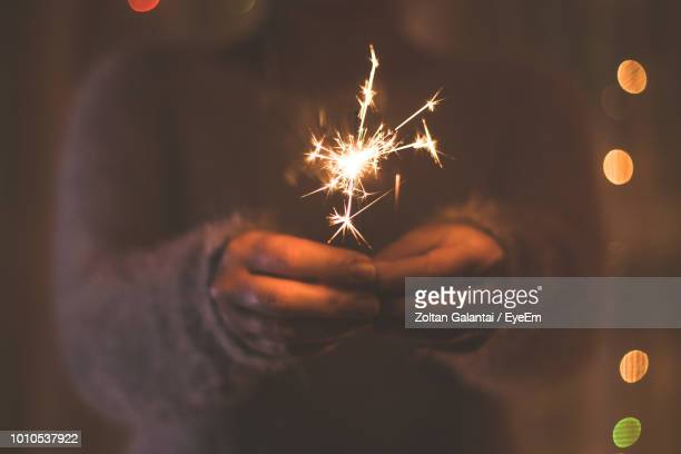 midsection of woman holding lit sparkler at night - sparks stock pictures, royalty-free photos & images