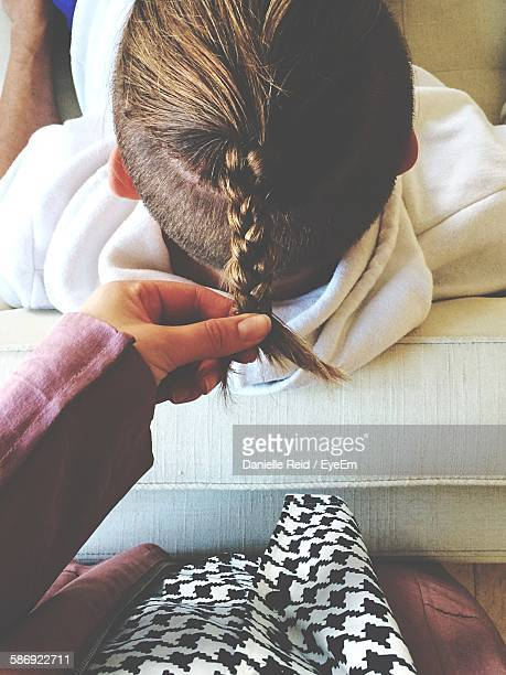 Midsection Of Woman Holding Man Braids