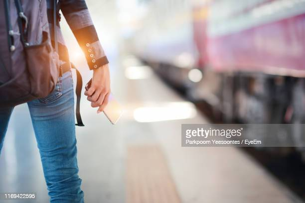midsection of woman holding mobile phone at railroad station - southeast stock pictures, royalty-free photos & images