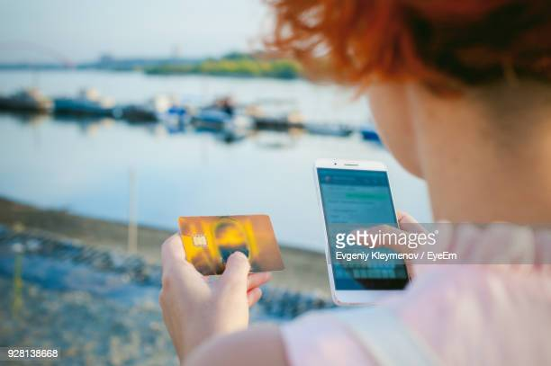 midsection of woman holding mobile phone - ginger banks stock pictures, royalty-free photos & images