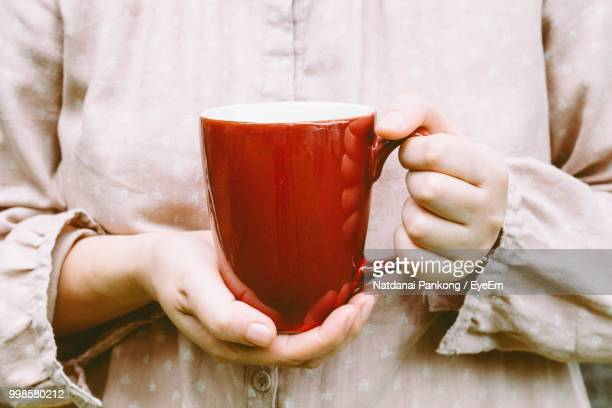 midsection of woman holding mug - mug stock pictures, royalty-free photos & images