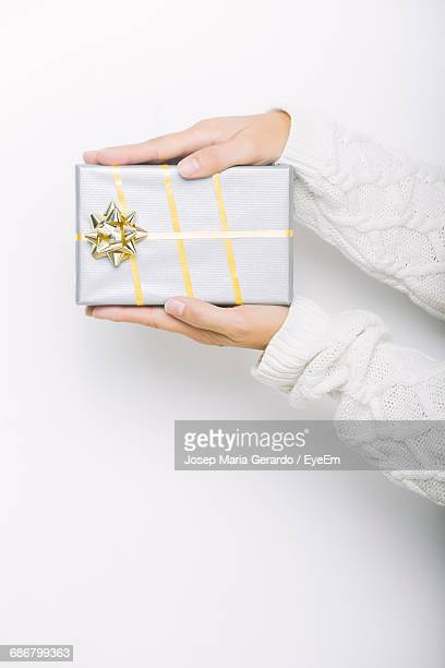 Midsection Of Woman Holding Of Christmas Present Against White Background