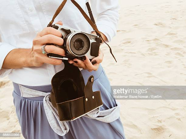 Midsection Of Woman Holding Old-Fashioned Camera At Beach