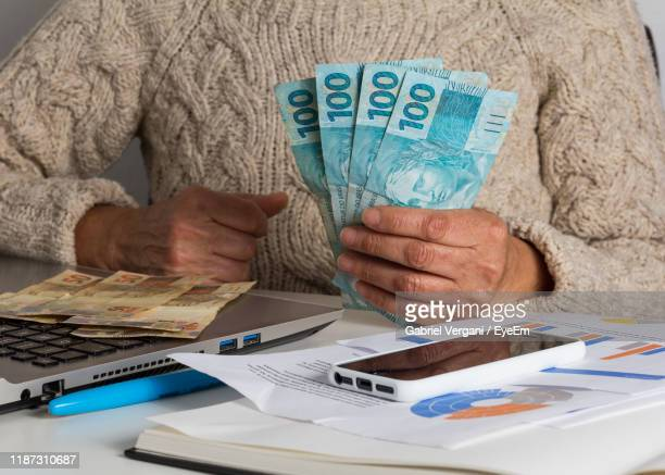 midsection of woman holding paper currency by objects on table - dinheiro real imagens e fotografias de stock