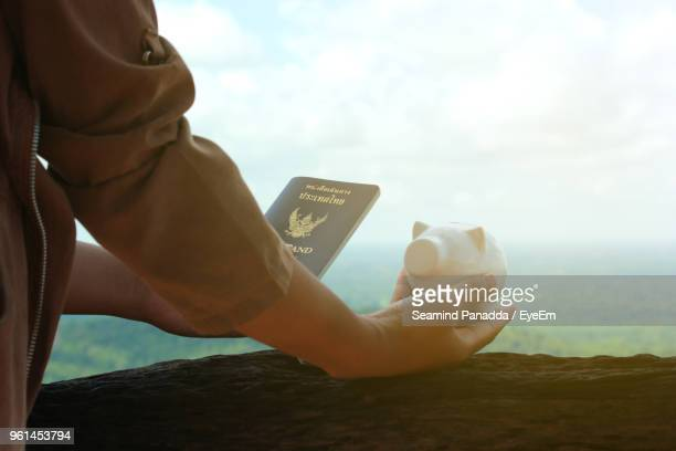 Midsection Of Woman Holding Passport And Piggy Bank Against Sky