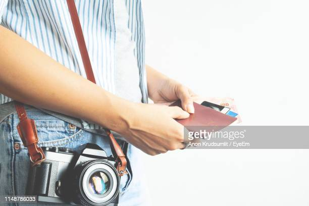 Midsection Of Woman Holding Passport With Paper Currency And Camera Standing Against White Background