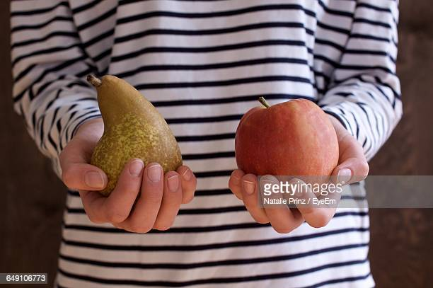 Midsection Of Woman Holding Pear And Apple