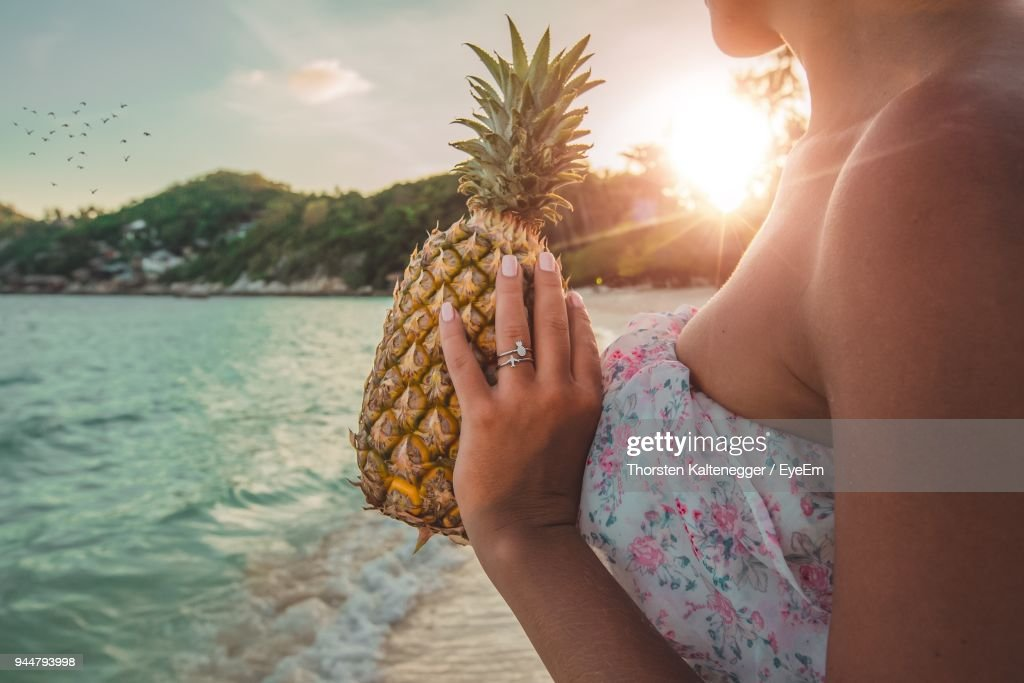 Midsection Of Woman Holding Pineapple At Beach Against Sky : Stock Photo