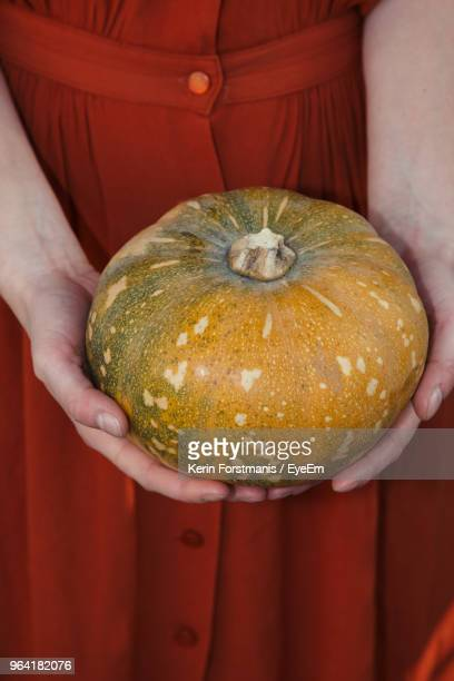 Midsection Of Woman Holding Pumpkin
