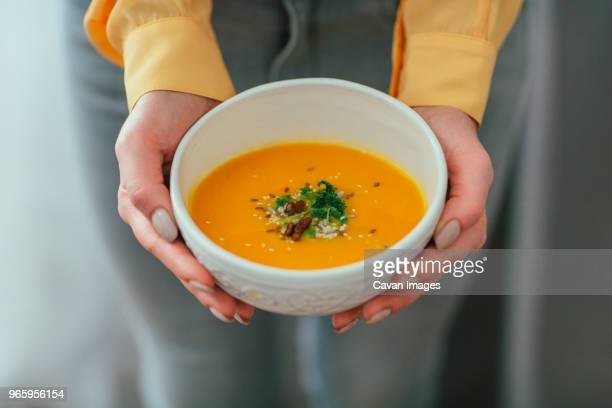 midsection of woman holding pumpkin soup bowl - soup bowl stock pictures, royalty-free photos & images