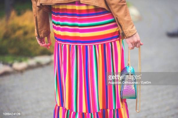 midsection of woman holding purse while standing on footpath - striped dress stock photos and pictures