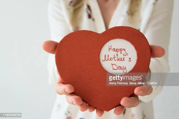 midsection of woman holding red heart shape on mother day - mothers day stock pictures, royalty-free photos & images