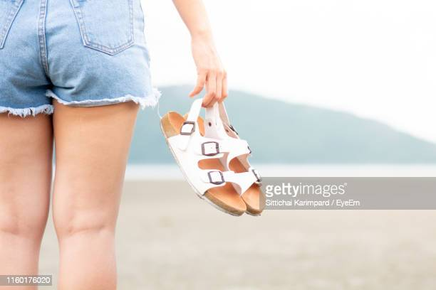 midsection of woman holding sandal while standing on beach - sandale stock-fotos und bilder