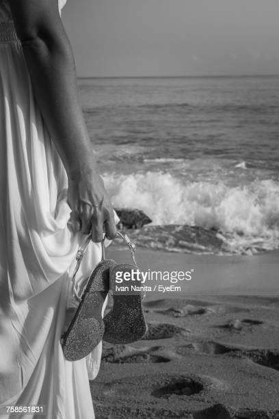 Midsection Of Woman Holding Sandal While Standing On Shore At Beach