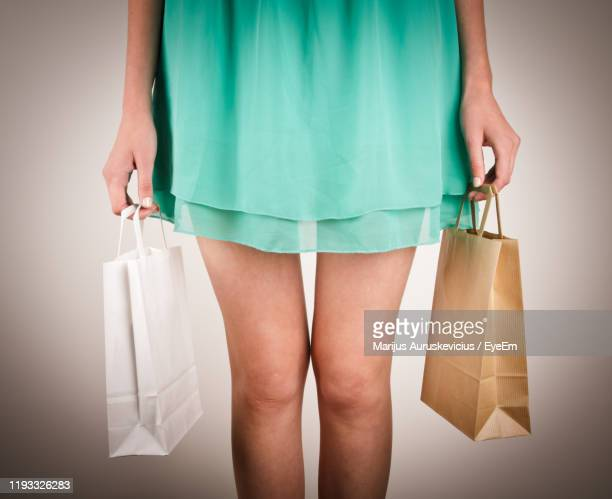 midsection of woman holding shopping bag while standing against gray background - azul turquesa fotografías e imágenes de stock