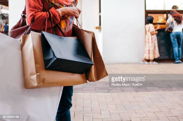midsection of woman holding shopping bags - shopping bag stock pictures, royalty-free photos & images