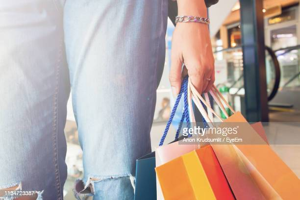 Midsection Of Woman Holding Shopping Bags While Standing In Mall