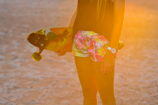 Midsection Of Woman Holding Skateboard While Standing At Beach During Sunset