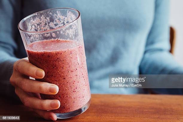 midsection of woman holding smoothie - smoothie stock pictures, royalty-free photos & images