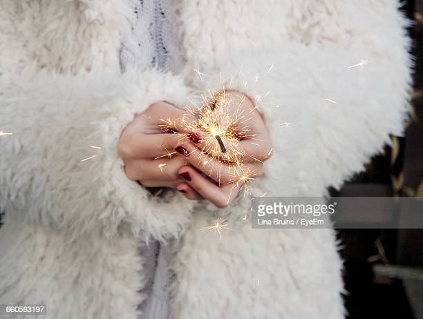 Midsection Of Woman Holding Sparkler