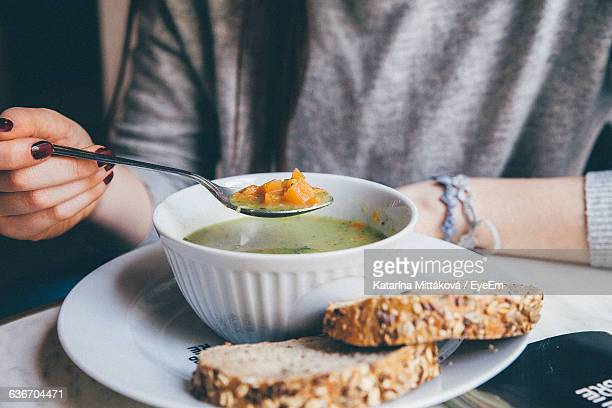 Midsection Of Woman Holding Spoon Over Soup