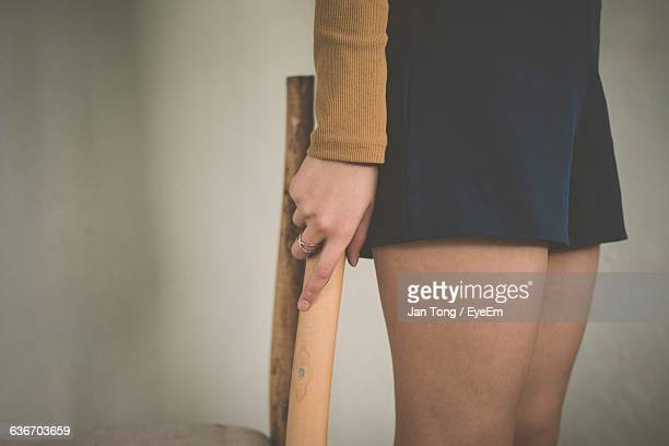 Midsection Of Woman Holding Stick While Standing Against Wall