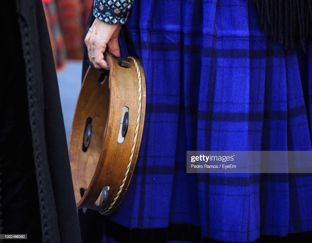 Midsection Of Woman Holding Tambourine : Stock Photo