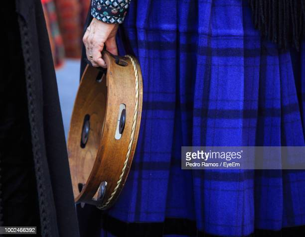 Midsection Of Woman Holding Tambourine