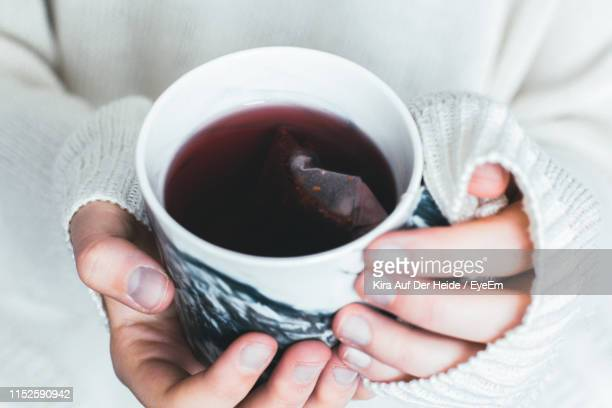 midsection of woman holding tea cup - black tea stock pictures, royalty-free photos & images