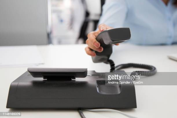 Midsection Of Woman Holding Telephone At Desk In Office