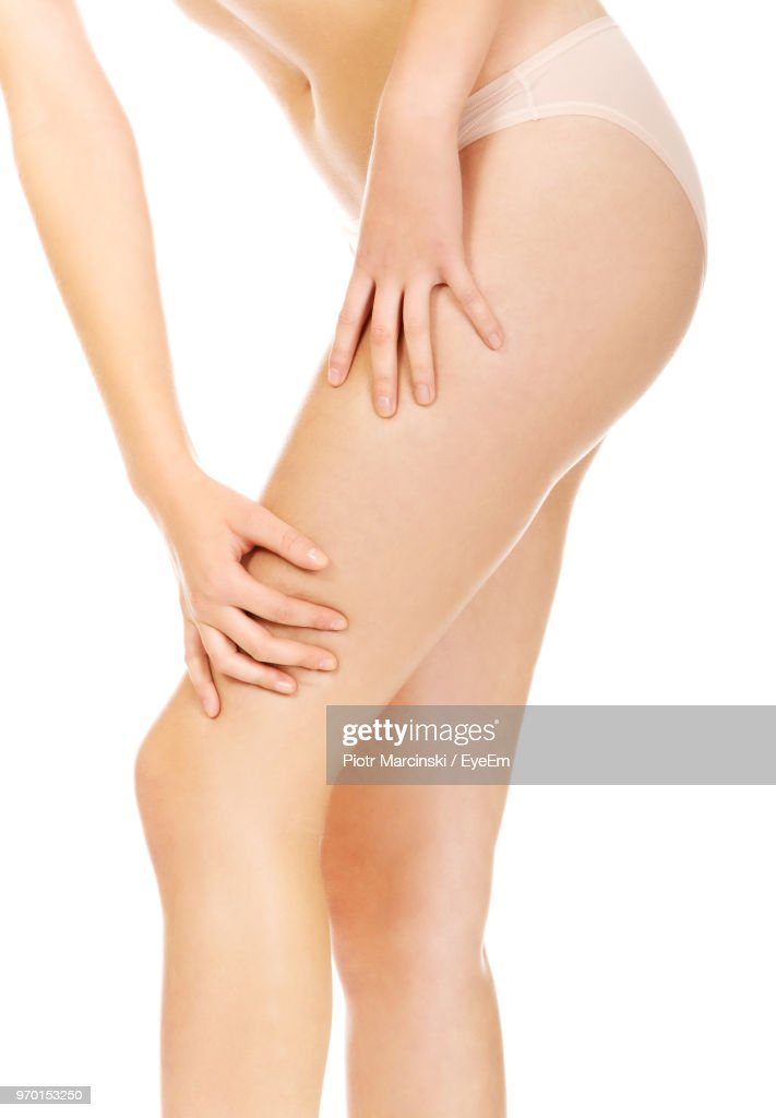 Midsection Of Woman Holding Thigh Against White Background : Stock Photo