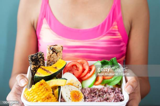 Midsection Of Woman Holding Various Food In Container