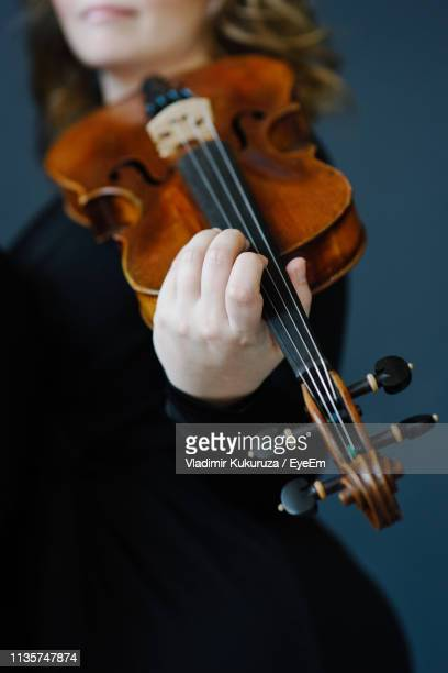 midsection of woman holding violin against gray background - violin family stock photos and pictures