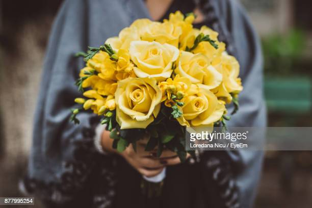 midsection of woman holding yellow rose bouquet - yellow roses stock photos and pictures