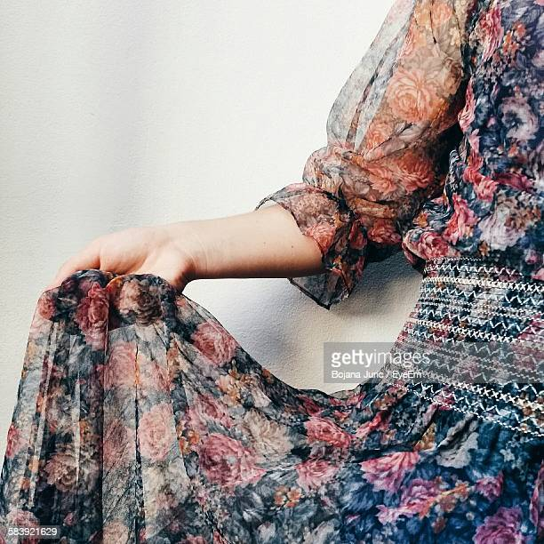 Midsection Of Woman In Dress Standing Against Wall