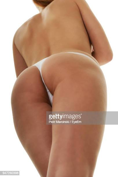 Midsection Of Woman In Panties Standing Against White Background